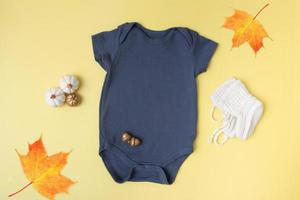 Baby clobodysuit mock-up with pumpkins on yellow background for your text or logo place in autumn season photo