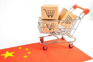 caja con el logotipo del carrito de compras y la bandera de China, importación, exportación, compras en línea o comercio electrónico, servicio de entrega de finanzas, tienda, envío de productos, comercio, concepto de proveedor. foto