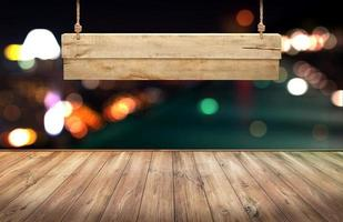Wood table with hanging wooden sign on city lights night blurred background photo