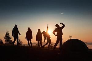 A silhouette of group people have fun at the top of the mountain near the tent during the sunset photo