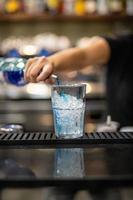 Mano de mujer vertiendo licor en un vaso. foto