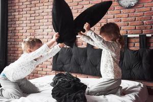 niños traviesos niño y niña organizaron una pelea de almohadas en la cama del dormitorio. les gusta ese tipo de juego foto