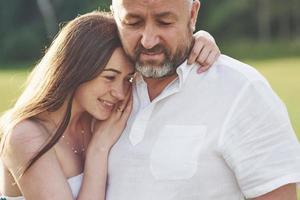 apuesto anciano y hermosa joven se abrazan, hija y su viejo papá pasan tiempo juntos al aire libre foto