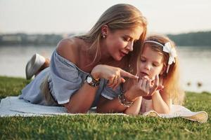 Attractive happy young mother lying with her cute daughter on the grass in the park. photo