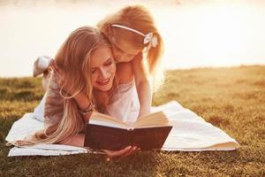 mother with a child reads a book on the grass photo