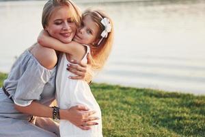 Madre joven feliz con una hija juguetona en un parque cerca del agua foto