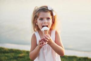 A beautiful little girl eats an ice cream near the water photo