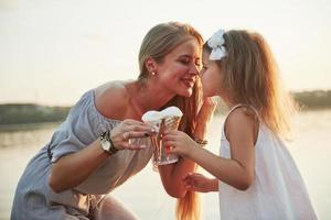 Mother and child eat ice cream in the park at sunset. photo