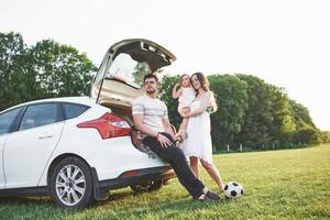 Pretty young married couple and their daughter are resting in the nature. The mother father and little girl are sitting on open car boot photo