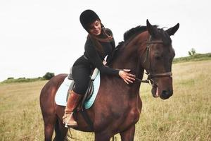 Young pretty girl - riding a horse, equestrian sport in spring time photo