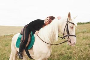 Young cute girl hugging her horse while sitting astride. She likes animals photo