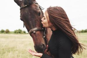 A happy girl communicates with her favorite horse. The girl loves animals andhorseback riding photo