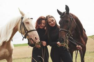 Two young beautiful girls in gear for riding near their horses. They love animals photo