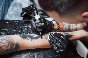 Close up tattoo machine. Master in black sterile gloves creating picture on hand with it in salon photo