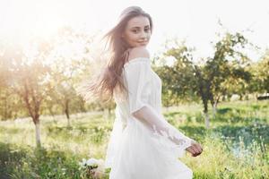 una niña con un vestido largo blanco está caminando en el jardín. hermosa puesta de sol a través de las hojas de los árboles foto