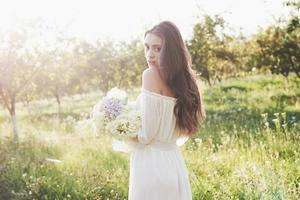 A beautiful young girl in a white light dress and a bouquet of summer flowers lays a fine day in the garden photo