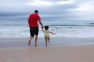 padre e hijo corriendo en la playa de verano. papá e hijo se divierten al aire libre. foto
