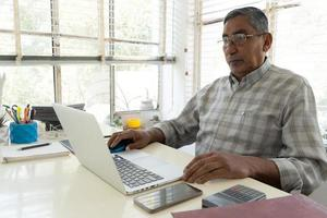 Portrait of confident businessman with laptop at desk in office photo