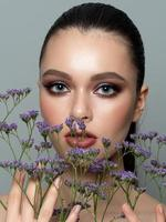 Portrait of young beautiful woman with flowers photo