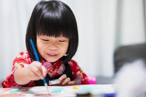 Happy Asian child painting water color on paper art. Sweet smile girl with lesson in class at homeschool. Kid wearing black apron uniform. Concept of learning according to preferences and aptitudes. photo