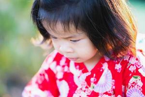 Close up, adorable 1-2 year old Asian girl is looking down at her path. A cheerful baby wears a red Japanese-style dress. During the summer or spring. photo