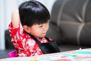 Cute child is reaching for her back scratching her back due to itching from a label attached to her clothes. Little girl wearing a red shirt and black apron. photo