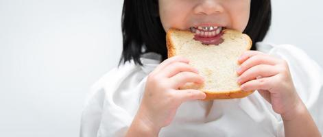Closeup. Child's hands holds the bread, kids teeth are bits chewing on the loaf of bread with gusto. photo