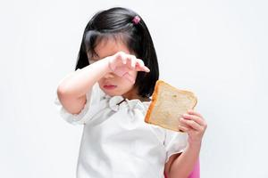 A cute little girl rubs her eyes from the back of her wrists due to itching or irritation. Child holding bread. Food concepts and food allergies. photo