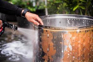 la mano de la persona que sostiene la manguera de agua para limpiar la suciedad y las manchas en el tanque de lavado. Limpia la parte interior de acero inoxidable para hilar. para reducir virus y bacterias. foto