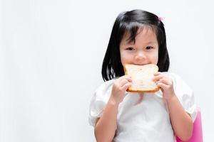 adorable niña sana sosteniendo un pan blanco frente a su cara. un niño hambriento está a punto de morder una barra de pan. sobre fondo blanco. foto