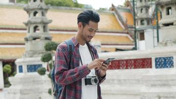 Asian man walking and using smartphone checking social media inside the temple of Thailand. video