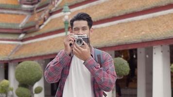 asiatische mann solo touristen, die im tempel spazieren gehen und sich im tempel umsehen und ein foto im tempel thailand machen. video