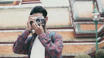 asiatische Touristen, die unterwegs sind und eine Filmkamera verwenden, um ein Foto im Tempel Thailands zu machen. video