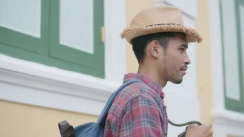 asiatischer Mann mit Filmkamera, der ein Foto beim Gehen auf der Straße in Thailand macht. video