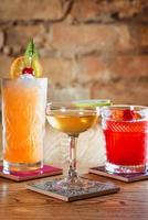 different colorful alcohol and non-alcohol cocktails in the glasses on the table photo