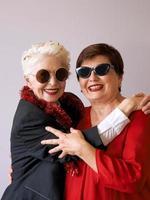 dos hermosas mujeres mayores maduras con estilo en gafas de sol abrazándose. diversión, fiesta, estilo, concepto de celebración foto