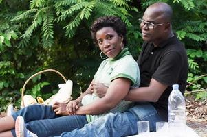 young couple sitting on a mat in the bush photo