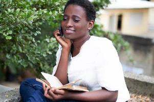 young woman calls with a book in hand photo