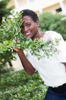 smiling young woman looking through foliage. photo