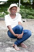 young woman sitting on a piece of brick. photo