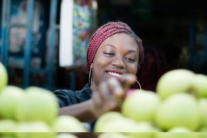 smiling young woman choosing apple  at street market. photo