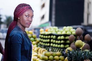 young woman standing in front of shelves of fruit to the market. photo