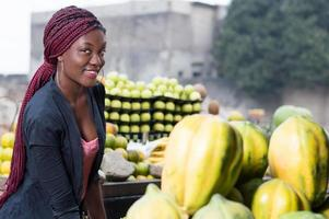 smiling young woman standing between fruit shelves. photo
