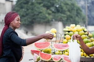 young woman buys fruit at the street market. photo