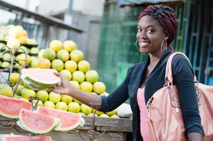 smiling young woman grabs a slice of ripe fruit. photo