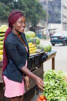 smiling young woman in front of vegetables photo