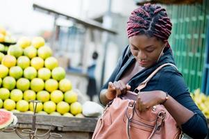 young woman in front of a pile of oranges, looking in handbag. photo