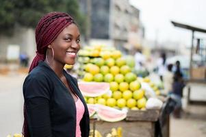 portrait of smiling young woman standing near fruit shelves. photo