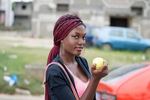 young woman holding an apple looking at the camera. photo