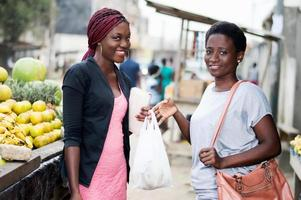 portrait of young smiling women standing in the fruit market. photo